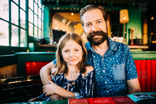 Father with arm around daughter in a restaurant