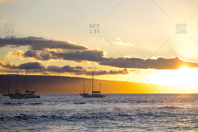 Two boats sailing into the sunset off the coast