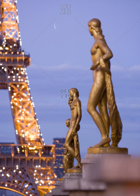 Paris, France - September 24, 2006: Statues by twinkling Eiffel Tower