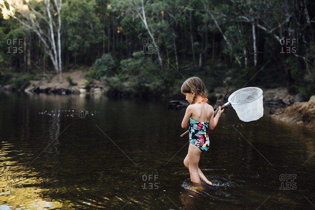 Girl standing in river with fishing net