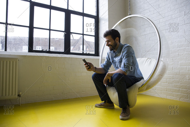 Smiling man sitting on swing in his loft looking at cell phone