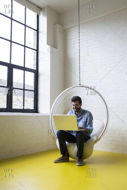 Smiling man sitting on swing in his loft using laptop
