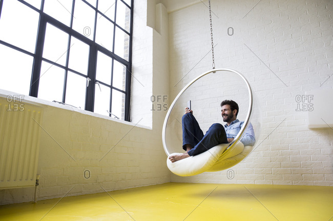 Smiling man sitting on swing in his loft taking selfie with smartphone