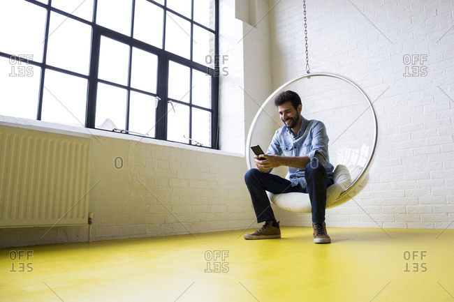 Young man sitting on swing in his loft looking at cell phone