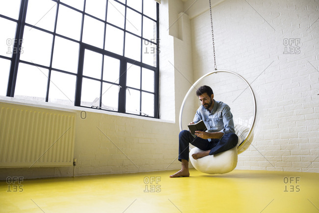 Young man sitting on swing in his loft reading a book