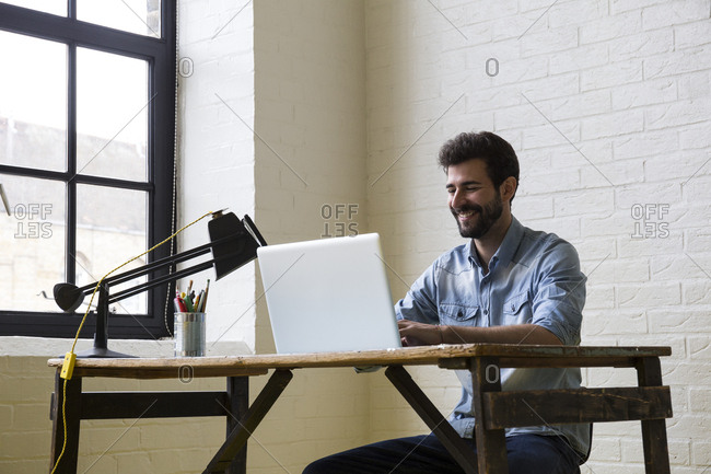Smiling man working at desk with laptop