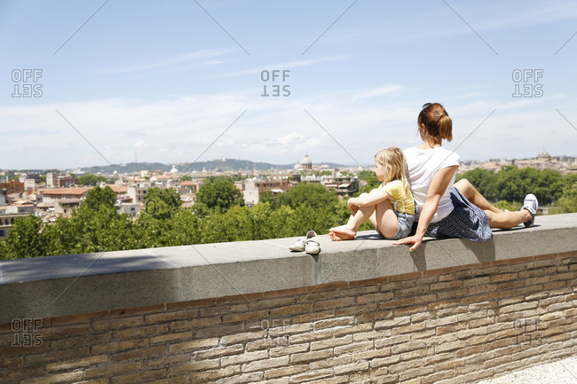 Italy- Rome- mother and her little daughter sitting back to back on a wall looking at view