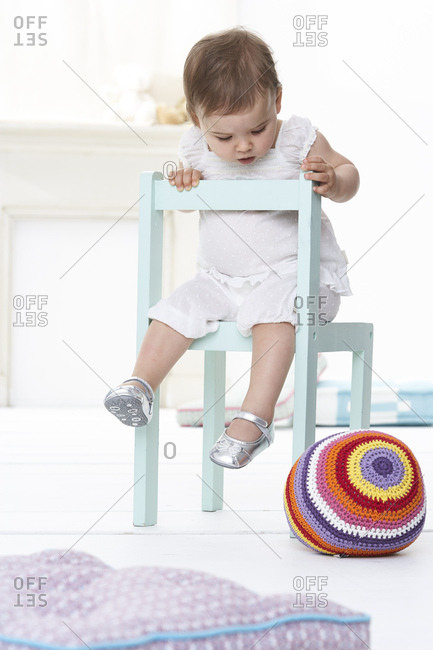 Baby girl sitting on chair looking down