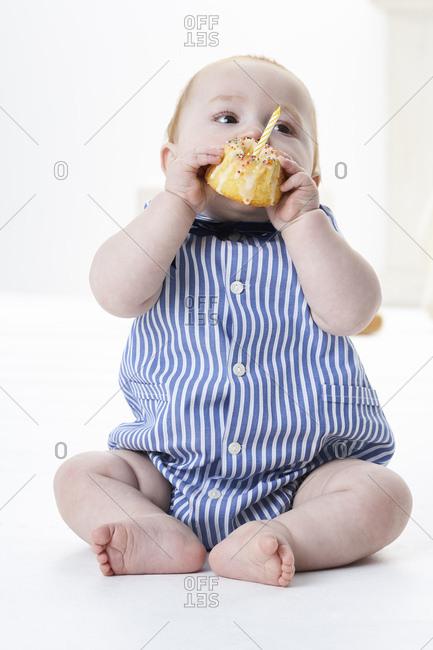Baby boy eating birthday cake