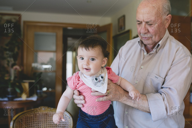 Happy Baby girl standing with help of Great-grandfather at home