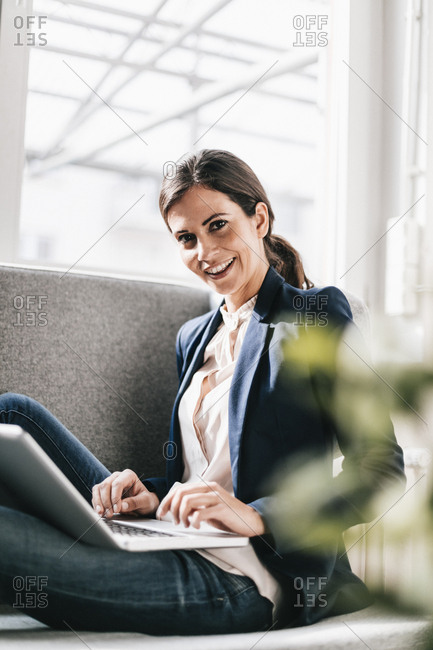 Portrait of smiling businesswoman using laptop on couch