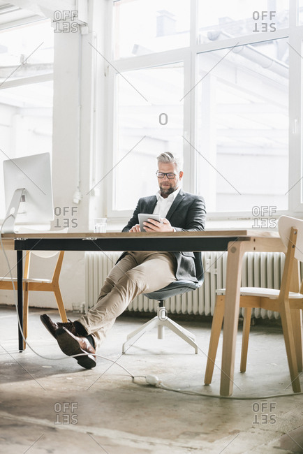 Businessman sitting relaxed in modern office