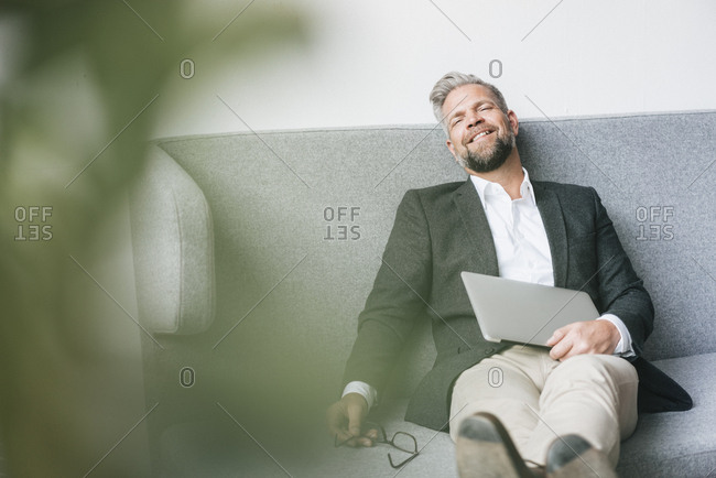 Businessman with laptop- relaxing on coach