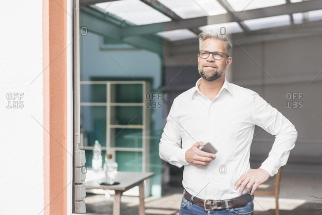 Businessman looking out of window- holding smart phone