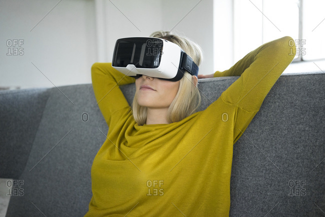 Woman sitting on couch wearing virtual reality glasses