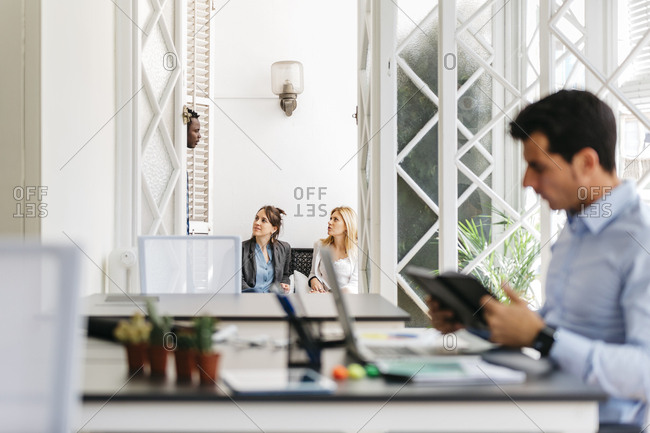 Business people talking on balcony while colleague is working