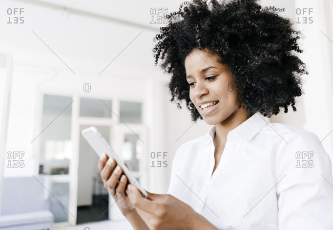 Young woman looking at her digital tablet for good news