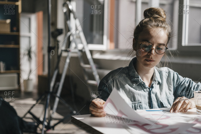 Young woman at table working on letter templates