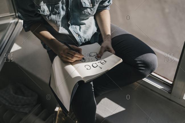 Woman writing letters in folder