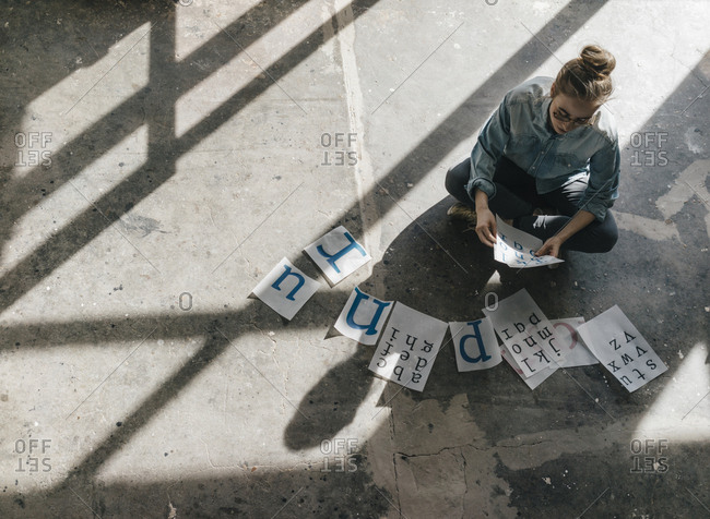 Young woman sitting on concrete floor working on letter templates ...