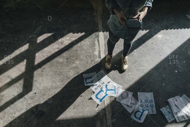 Woman standing on concrete floor using tablet and working on letter templates