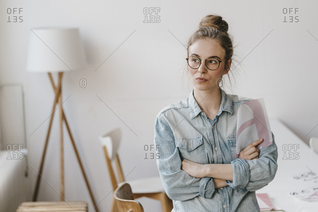 Young woman holding letter template looking sideways