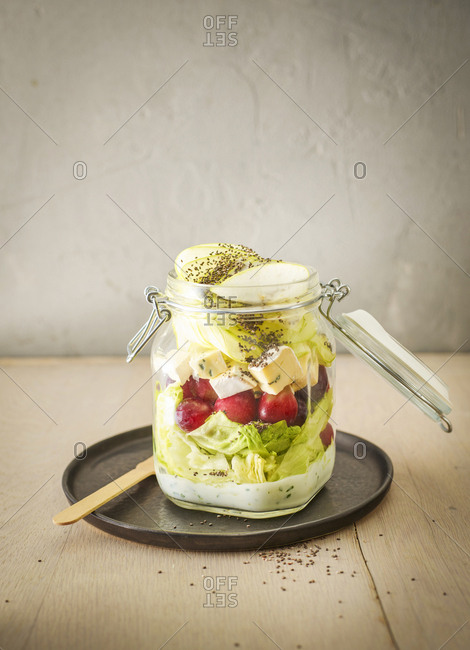 Preserving jar of iceberg salad with grapes- apple- blue cheese and chia seeds