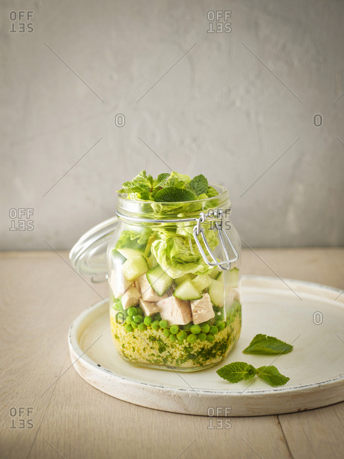 Preserving jar of Couscous salad with peas- cucumber and diced boiled chicken