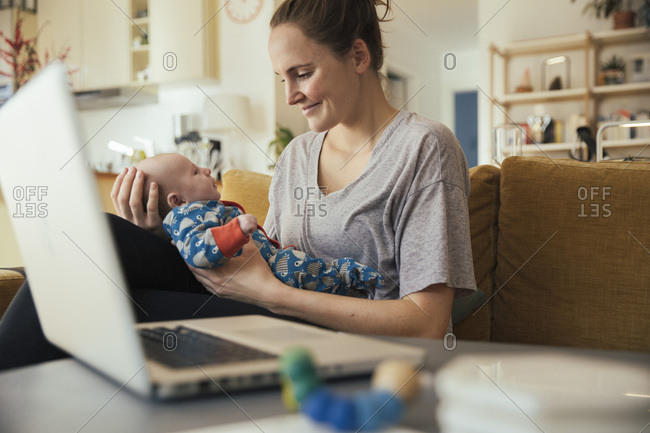 Mother holding her newborn baby at home next to laptop