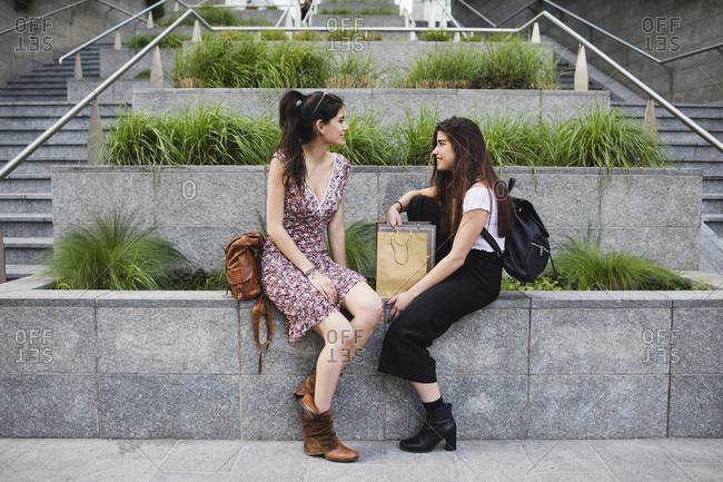 Two young women sitting down and talking in the city