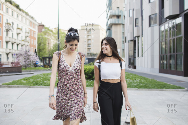 Two happy young women walking in the city