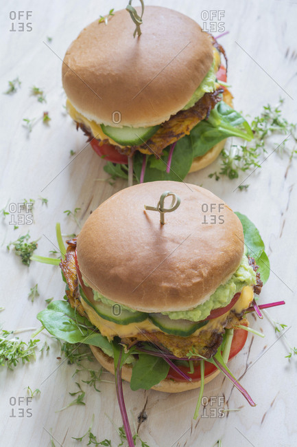 Two veggie burgers with sweet potato patties- avocado dip- cheese and vegetables