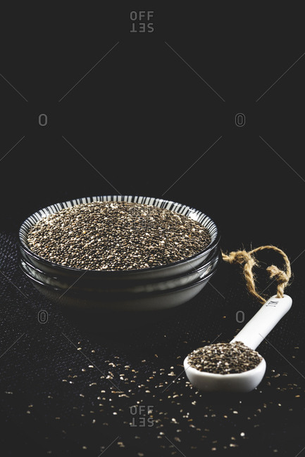 Bowl and mass of black chia seeds on black ground