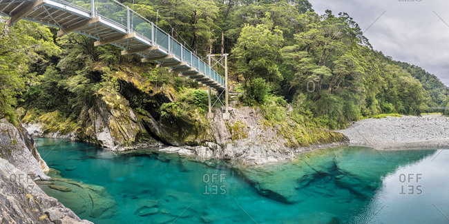 New Zealand- South Island- Mount Aspiring National Park- Blue pools at Makarora river with suspension bridge