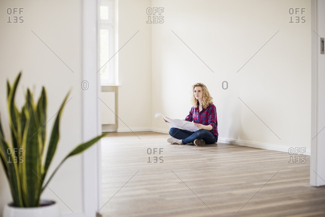 Young woman in new home sitting on floor with plan