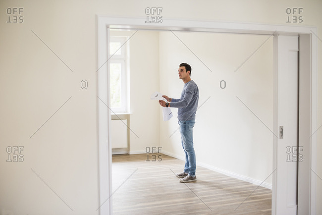 Young man in new home holding plan