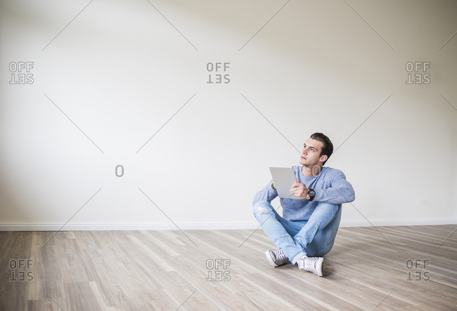 Young man in new home sitting on floor with tablet