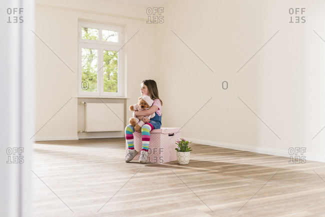 Girl in empty apartment holding teddy