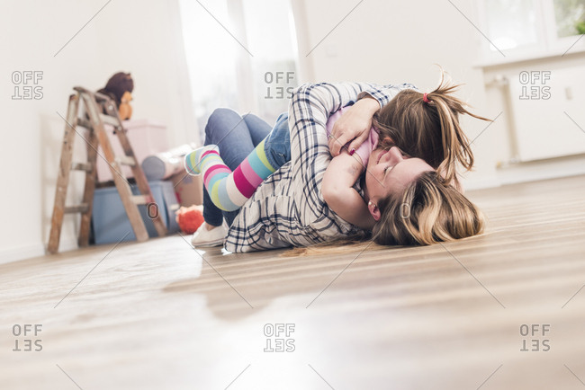 Mother and daughter hugging on the floor in new home