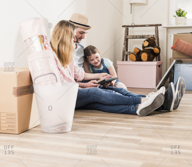 Parents and daughter using tablet in new home