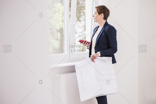 Woman in new apartment with plan and cell phone looking out of window