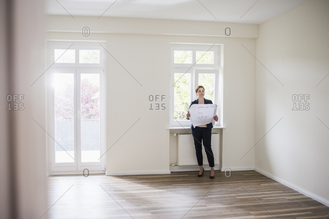Woman in empty apartment with plan