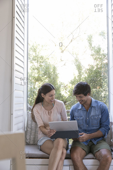 Smiling young couple sitting on windowsill sharing tablet