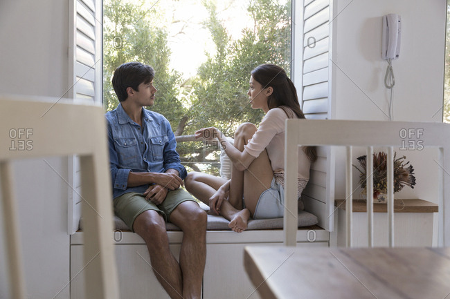 Young couple talking on windowsill