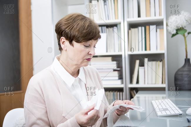 Senior woman sitting at table- checking bills