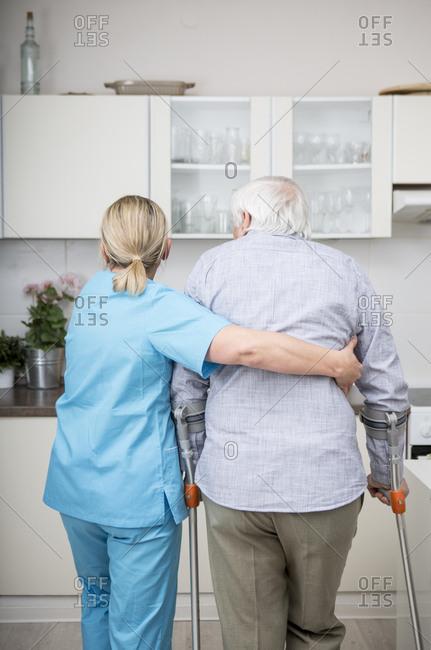 Geriatric nurse supporting week patient