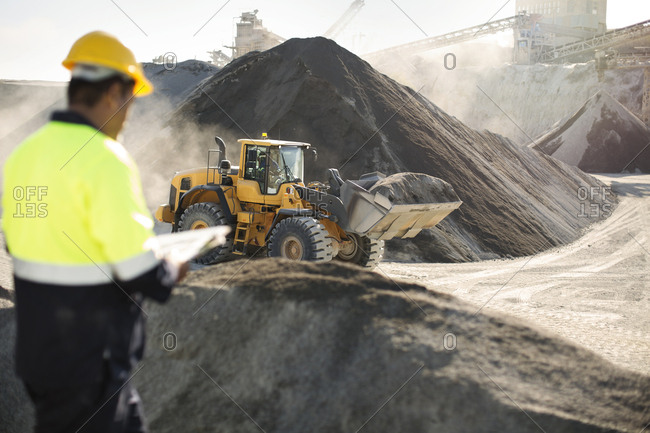 Worker standing at quarry- using clipboard