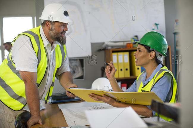 Female quarry worker checking files in office