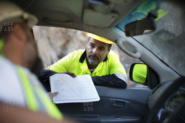 Worker handing over documents to colleague sitting in car