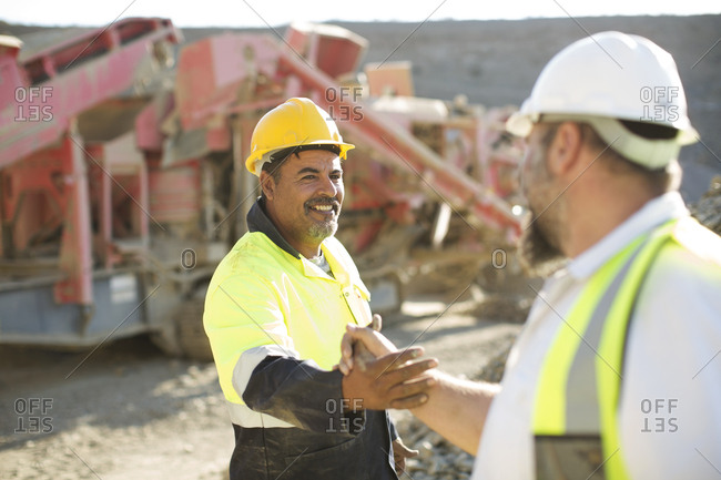 Two quarry workers shaking hands